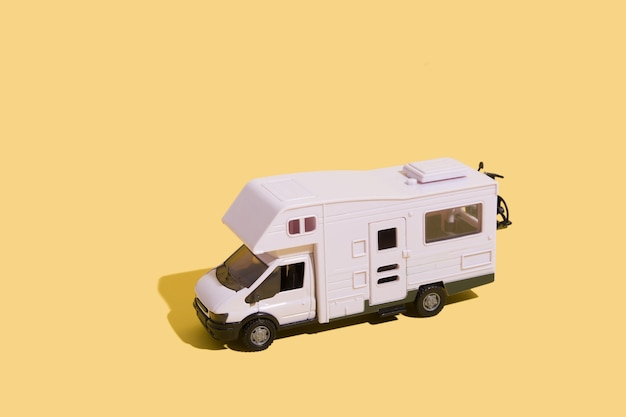 Toy van on a yellow background minimalistic summer family vacation concept
