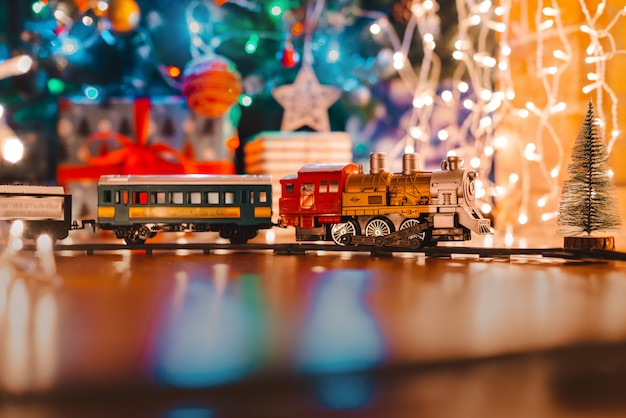 Toy vintage steam locomotive on the floor under a decorated christmas,  bokeh lights garland.