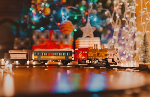 Toy vintage steam locomotive on the floor under a decorated christmas tree on a background of bokeh lights garland