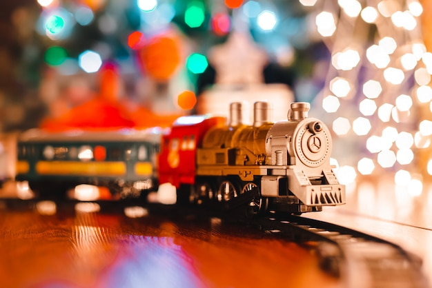 Toy vintage steam locomotive floor under a decorated christmas tree   bokeh lights garland.