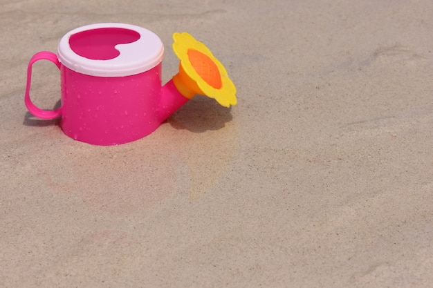 Toy watering can on the sand of the sea coast.
