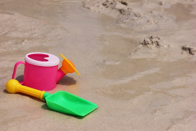 A toy watering can and a toy shovel are located on the sand of the sea coast.
