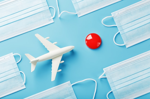 A toy white airplane and protective masks on a blue surface with a red dot as the destination