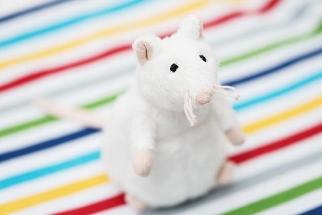 Игрушка белая крыса на фоне красочных полос.