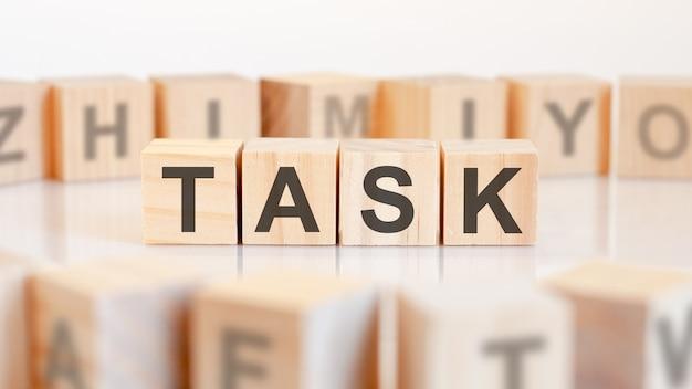 明るい背景、選択的な焦点とテーブルの上の文字タスクとおもちゃの木のブロック。文字が周りにあるおもちゃのブロック。セレクティブフォーカス。