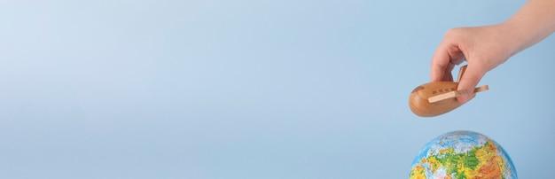 Игрушка деревянный самолет самолет пролетел над земным шаром, путешествуя концепции. размер баннера.