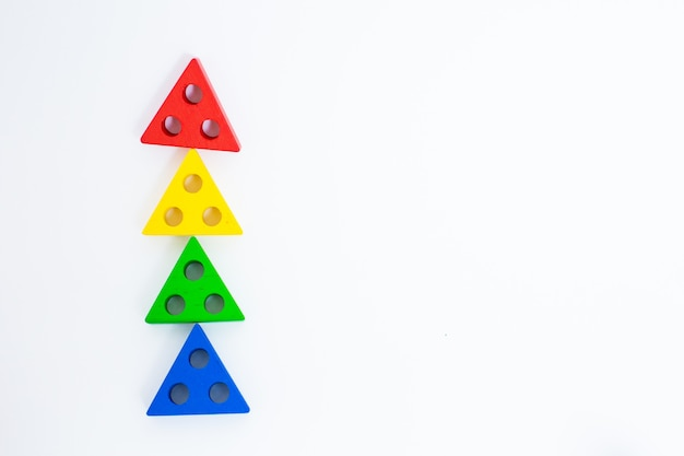 Toy wooden blocks, multicolor building construction bricks looking like christmas tree. white background. early education