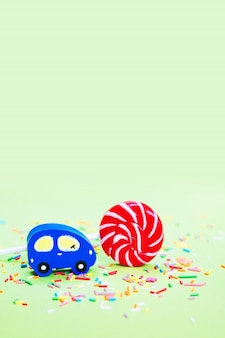 Toy wooden blue car and lolipop with confetti on green