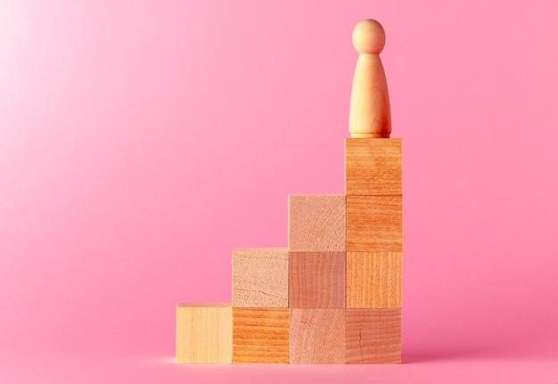 ピンクの背景のおもちゃの木製の立方体