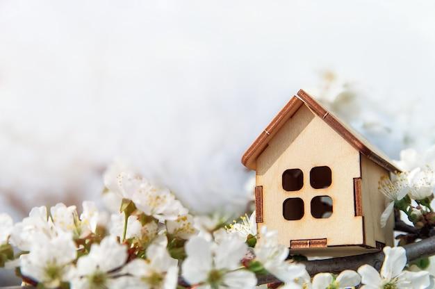 장난감 목조 주택과 벚꽃 꽃 봄 자연 배경 및 복사 공간 개화 나무 모기지 건설 임대 가족 및 재산의 개념