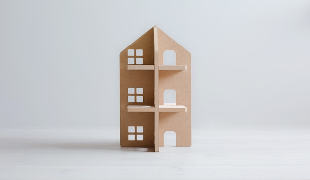 Toy wooden house on white wooden floor and bright background.