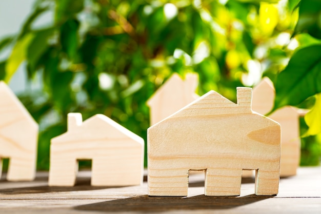Toy wooden house on wooden table against foliage background, front view