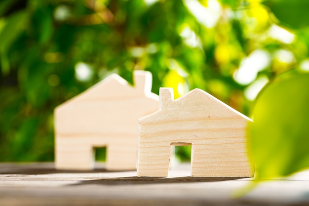 Toy wooden house on wooden table against foliage background