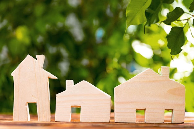 Toy wooden house on wooden table against foliage, front view