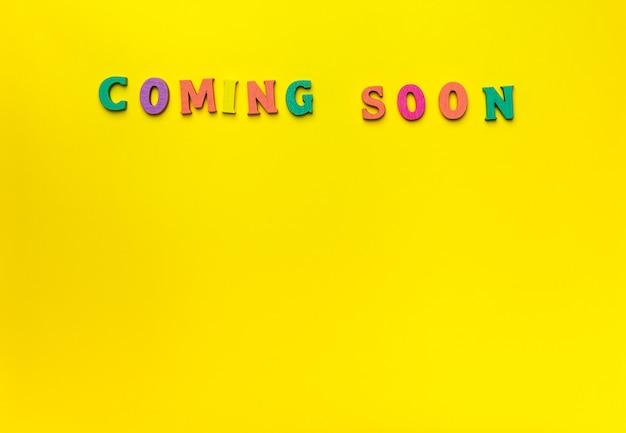 黄色の背景で近日公開予定のおもちゃの木製の手紙