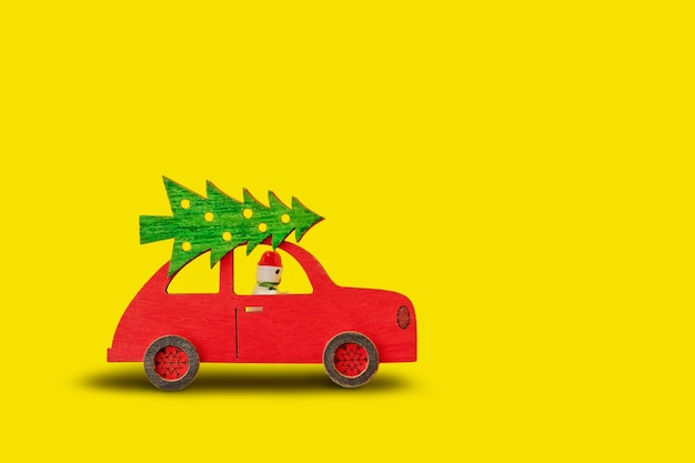 Toy wooden red car with christmas tree on the roof and snowman at the wheel on yellow background
