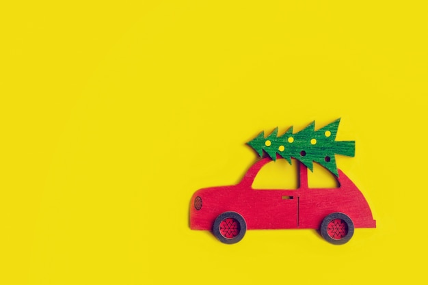 Toy wooden red car with christmas tree on the roof on yellow background, for mockup or design