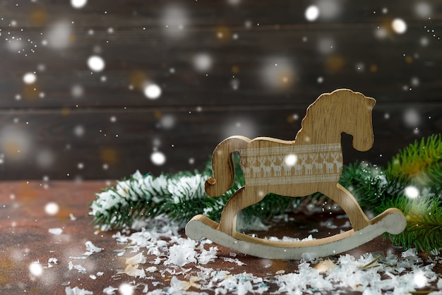 Toy wooden rocking horse as of new year's decorations with snow and fer tree