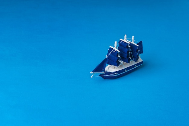 A toy wooden sailboat on a dark blue surface imitating the sea. the concept of travel and adventure.