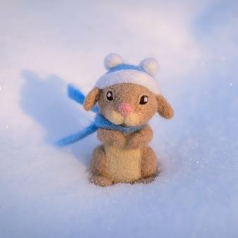 Игрушка валяная из шерсти милый кролик, заяц в синей шапке и шарфе стоит на снегу в солнечный зимний день