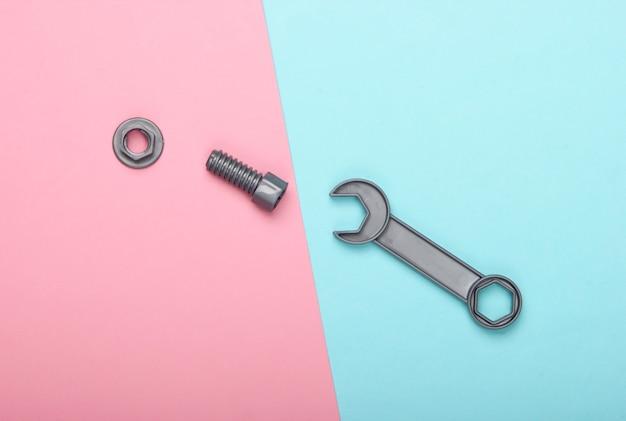 青ピンクのパステル背景にボルトでおもちゃのレンチとナット。上面図