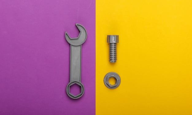 紫黄色の背景にボルトでおもちゃのレンチとナット。上面図