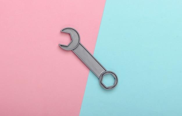 青ピンクのパステルカラーの背景におもちゃのレンチ。上面図