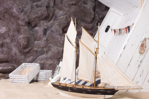 Игрушечная яхта и разбитый деревянный корабль в морском или морском натюрморте на песчаном пляже у подножия скалистого обрыва с деревянными ящиками от груза в концептуальном изображении