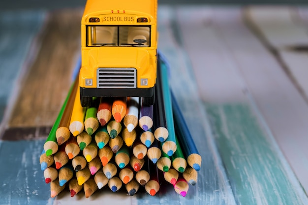 Toy yellow bus on bunch of colored pencils .