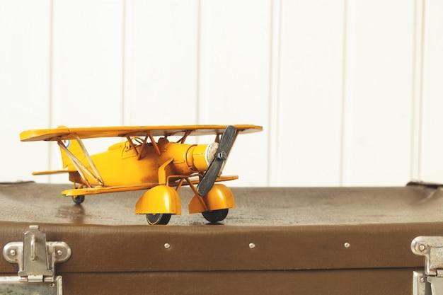 Toy yellow metal plane old retro suitcases white wood vintage tinting