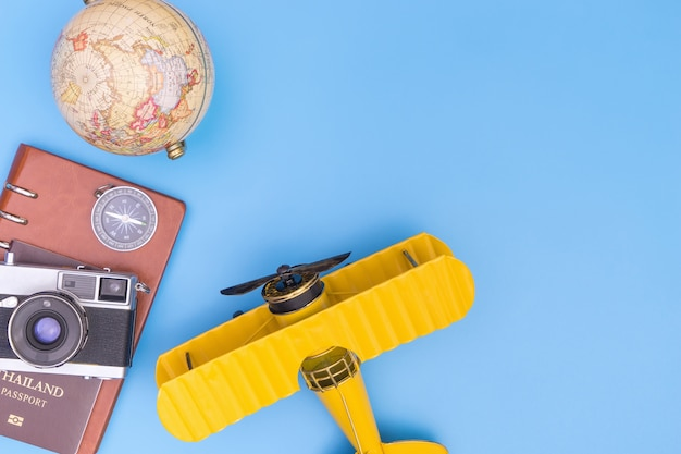Toy yellow plane with travel object for blue travel copy space travel concept