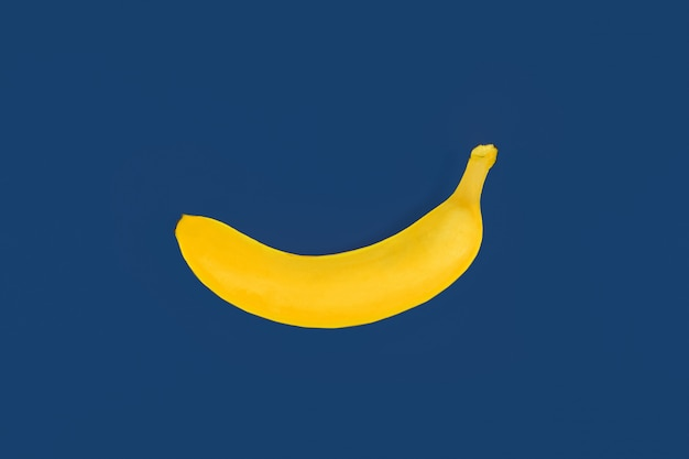 Toy yellow plastic banana on blue colored background