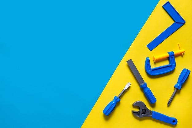Фон игрушки. вид сверху игрушечных инструментов на синем фоне.