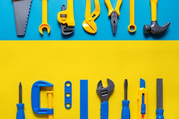 Фон игрушки. вид сверху игрушечных инструментов на синем желтом фоне с копией пространства для текста.
