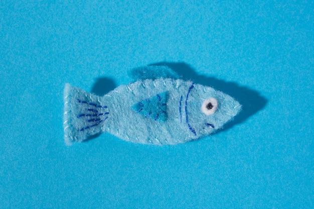 파란색 배경에 느낌으로 만든 물고기 손의 형태로 장난감. 손 바느질