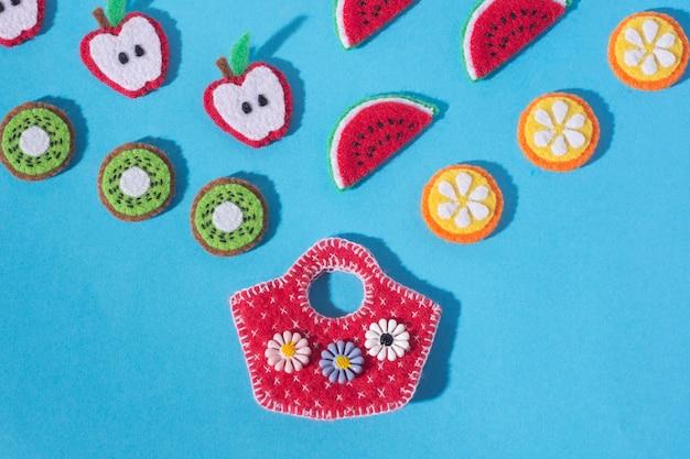 파란색 배경에 느낌으로 만든 음식과 과일 손의 형태로 장난감. 손 바느질