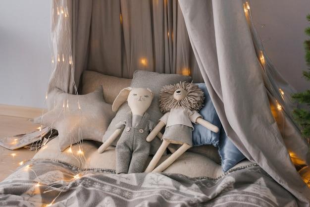 Игрушки на кровати в окружении подушек на детской кроватке в окружении рождественских огней