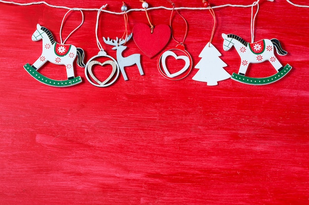 Toys on a red wooden background deer, horse, balls, tree, heart - made of wood Premium Photo