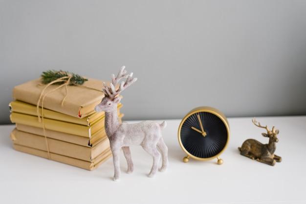 Toys souvenir christmas reindeer, a stack of books and a table clock in the decor of the house