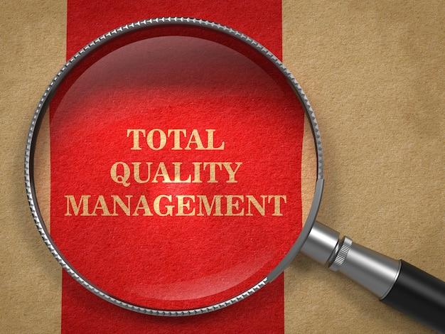 Tqm-総合的品質管理の概念。赤い縦線のある古い紙の虫眼鏡。