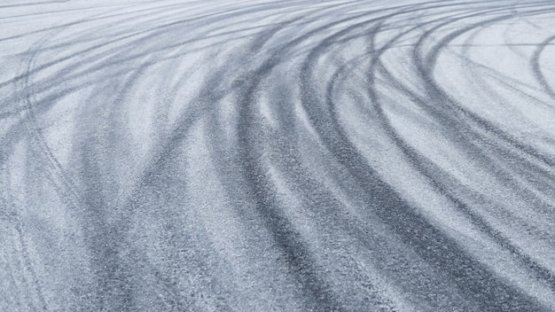 Traces of car tires on the asphalt close up road background