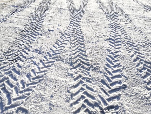 明るい太陽の下で雪の中で車のタイヤの痕跡