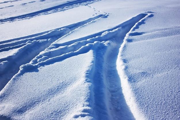 雪の上の車のタイヤの痕跡