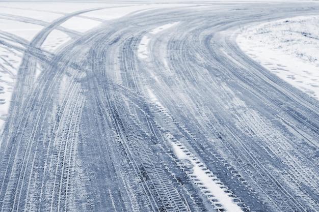 Следы автомобиля на заснеженной дороге зимой