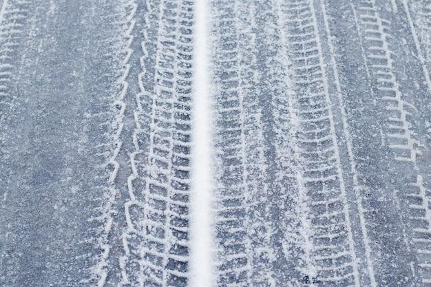겨울에 눈 덮인 도로에 자동차의 흔적
