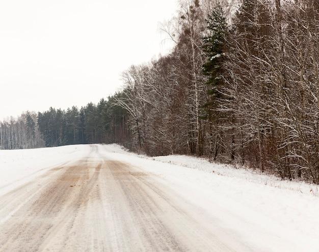 눈 위의 트레드 흔적, 도로의 겨울 시즌에 덮인 눈, 클로즈업 촬영, 하늘과 프레임의 나무