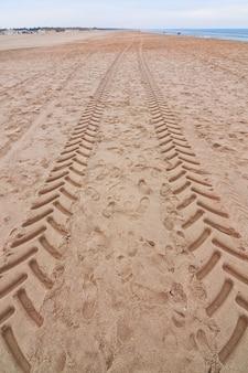トレース、ビーチの海の近くの砂の上のトラクターの兆候。