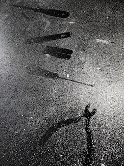 Traces of tools on a black table dusted with white dust