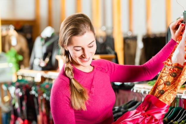 Женщина покупает tracht или dirndl в магазине