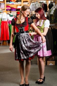 女性は店でtrachtまたはギャザースカートをしようとしています。